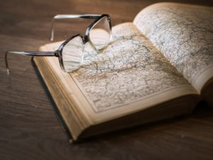 glasses on an open book with a map inside