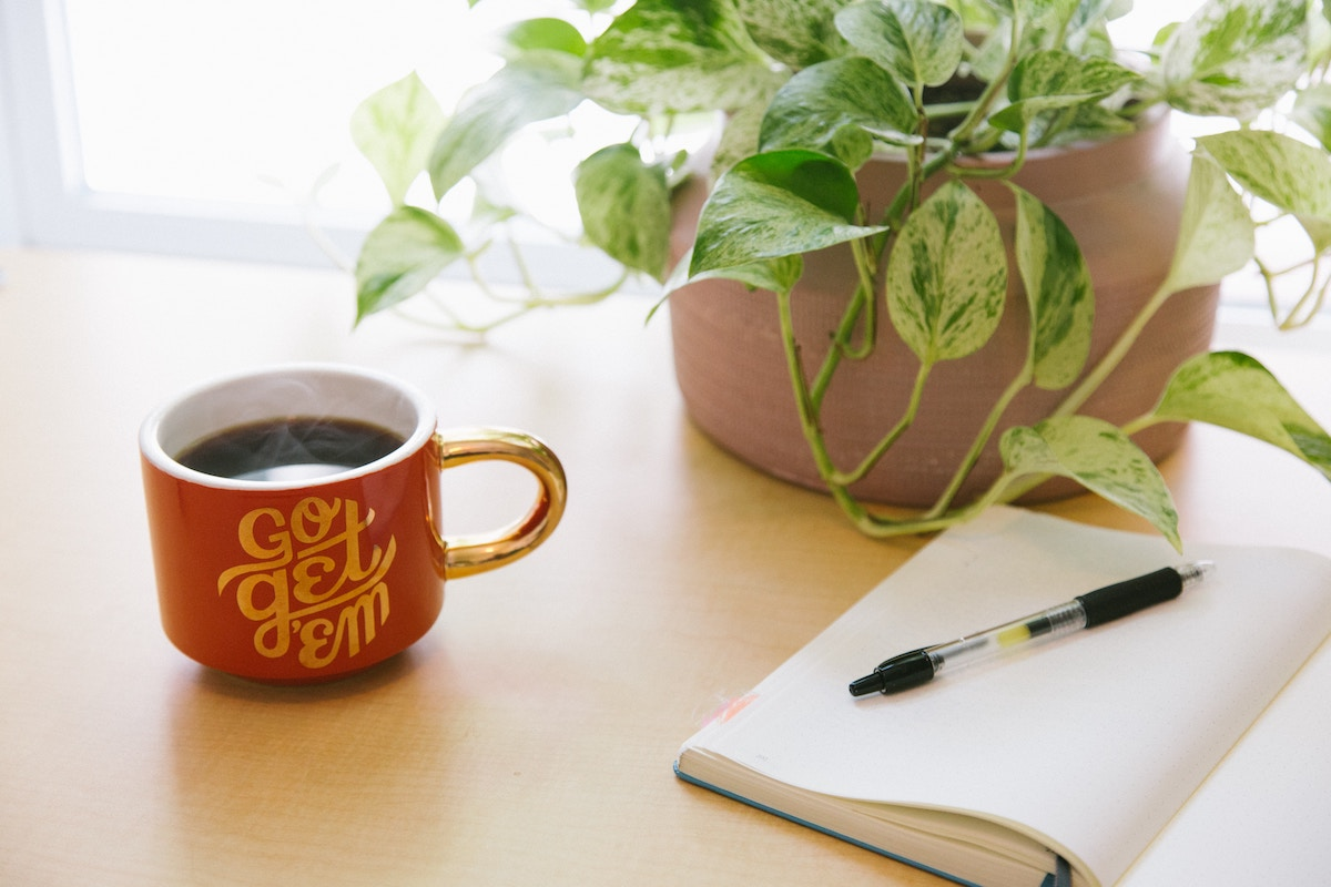 """coffee in mug reading """"go get 'em"""" on table with plant and writing book"""