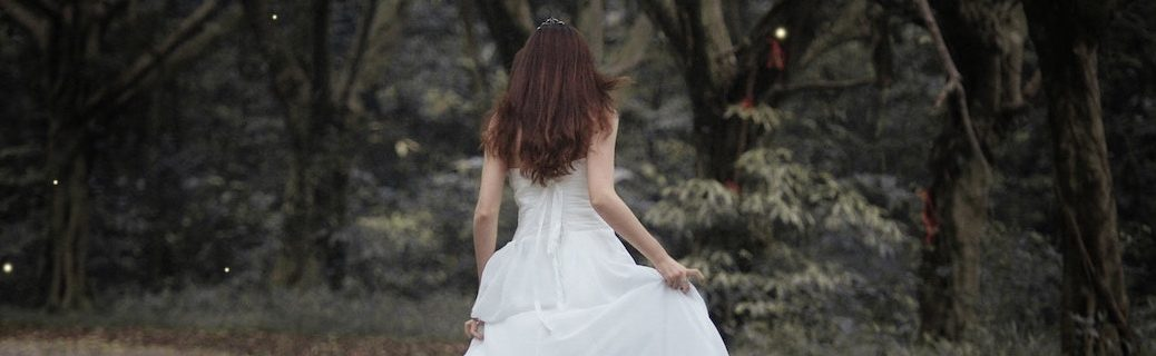 woman in fancy white dress running away on forest path, with sparkles in the air
