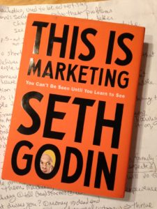 "cover of book ""This Is Marketing"" which is mostly text, with a face in one letter"