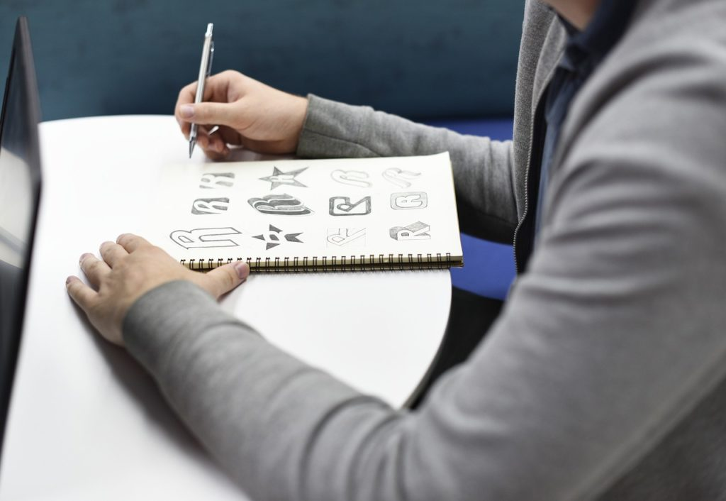 person holding pencil, drawing logos with the letter R in a sketch pad