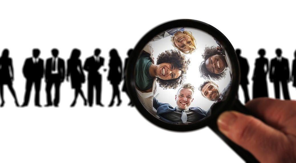 row of silhouettes in back, a hand is holidng a magnifying glass that is showing five smiling people