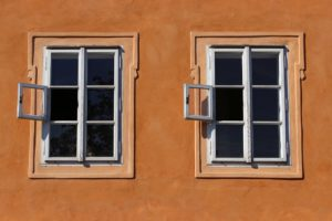 two identical 6-paned windows in an adobe-like wall