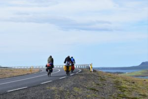 bicyclists cycling along a coastal road with packs