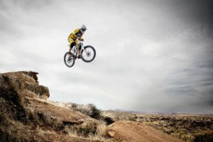 a mountain biker leaping off a rock