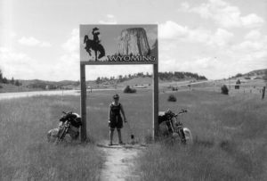 "woman standing in grass under sign that says ""Wyoming"""