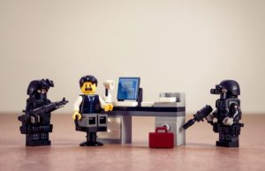 lego man at desk with lego police surrounding him