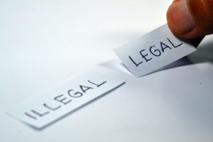 words illegal and lega on paper with fingers choosing legal
