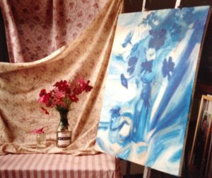 a vase of flowers and a painting of the flowers with only blue paint