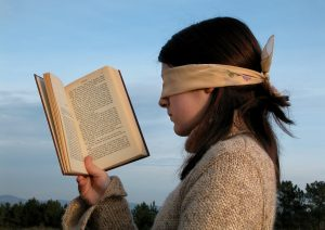 blindfolded woman holding a book open