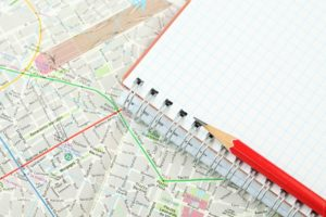 pencil and blank notebook on top of map of city
