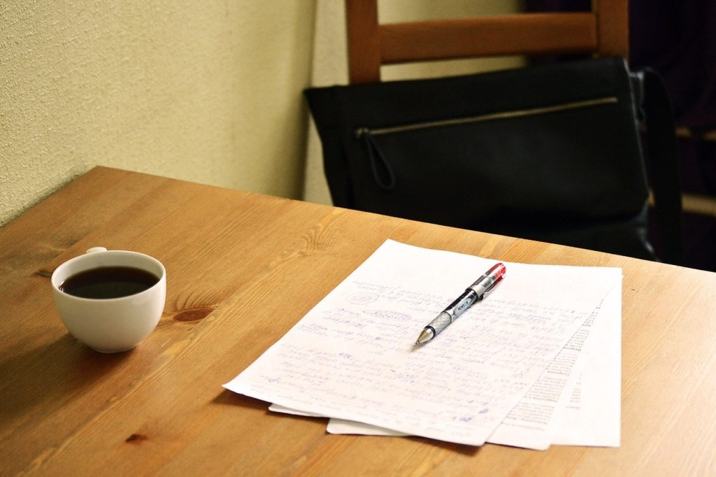 papers with red pen on table, with coffee
