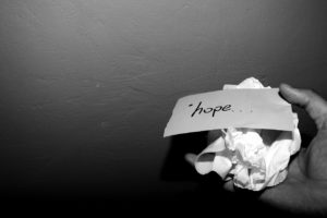 crumpled paper with the word hope, in a hand